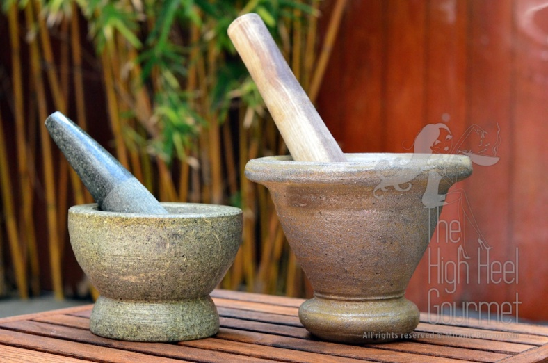 "Left: The granite mortar with granite pestle. This is a must-have tool in every common Thai household. Even more so than a rice cooker, because we can cook rice in a regular pot but can't live without these. Right: The terra cotta mortar with wooden pestle. This is good for making ""Som Tam"" or papaya salad, NOT for curry paste. The pestle isn't heavy enough to grind the ingredients, and if you tried to pound them hard enough the mortar will break."